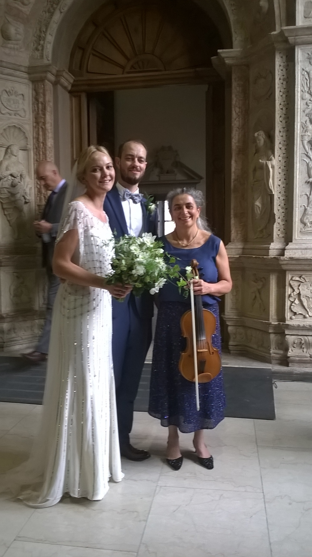 The newly wedded couple and the wedding musician with the viola, in the beautiful Town Hall of Cremona, in Italy, the homeland of the finest stringed musical instrument