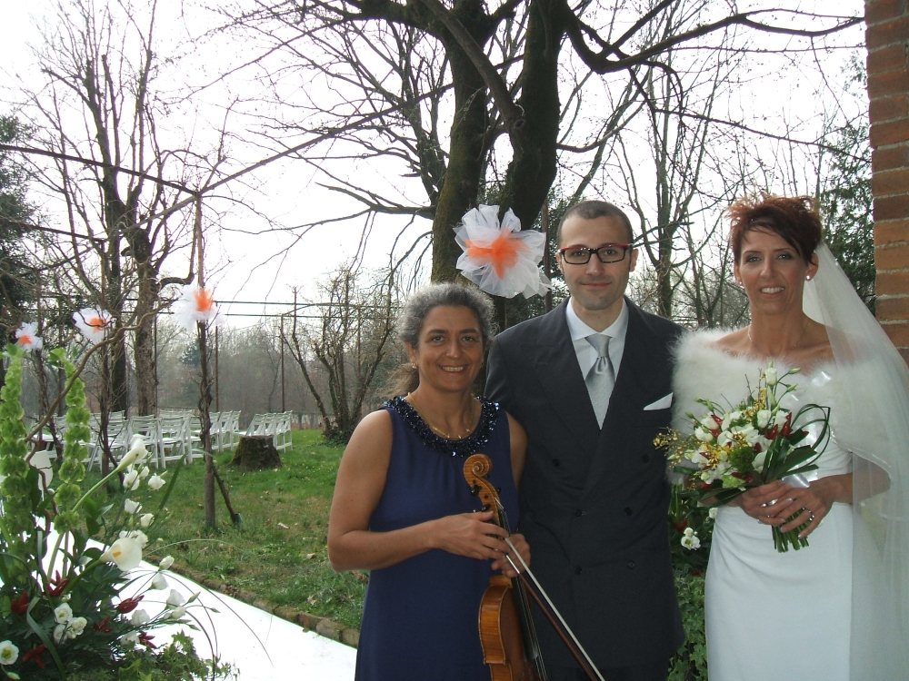 Bride and groom with wedding musician after their civil wedding ceremony in the garden of a castle, near Milan, Italy